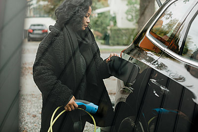Mid adult woman with electric car at charging station seen through glass - p426m2194972 by Maskot