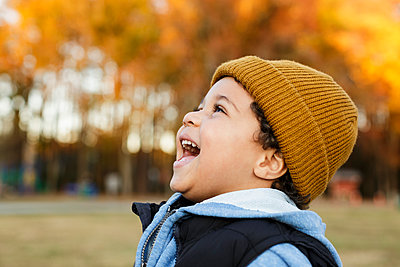 Mixed Race boy laughing in park - p555m1219612 by Roberto Westbrook
