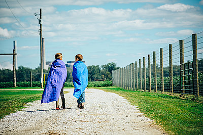 Caucasian children wearing capes on dirt road - p555m1412589 by Inti St Clair