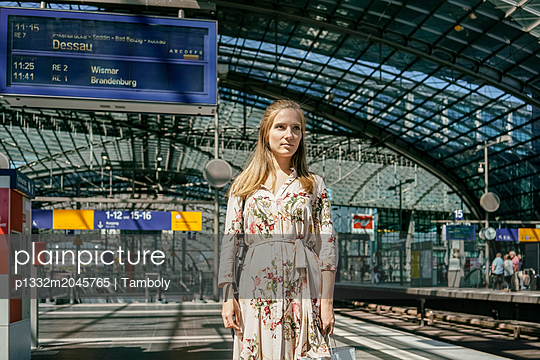 Young woman at a train station waiting for a train - p1332m2045765 by Tamboly