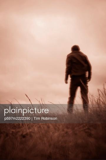 Man walking purposefully through grassy field - p597m2222390 by Tim Robinson