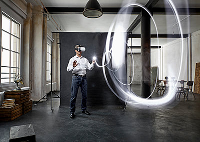 Mature man with vr glasses light painting in front of black backdrop in loft - p300m1581145 von Philipp Dimitri