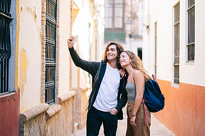 Smiling young couple taking selfie while standing on narrow street at Santa Cruz, Seville, Spain - p300m2188226 by Daniel González