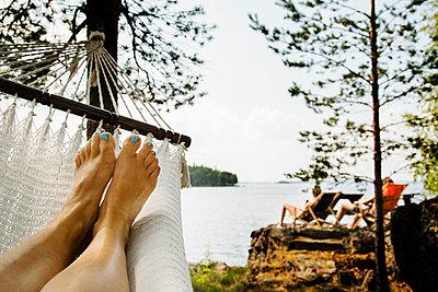 Sweden, Dalarna, near Falun, Lake Runn, Young woman relaxing in hammock by lake - p352m1061646f by Lena Katarina Johansson