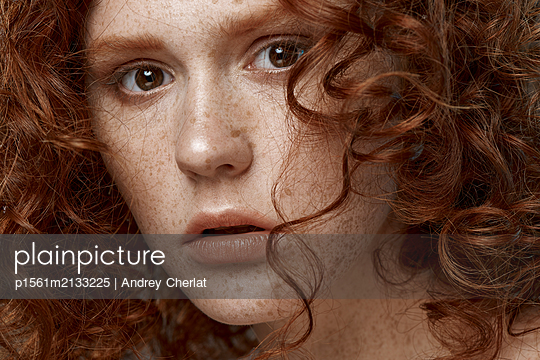 Red haired girl with freckles look at the camera - p1561m2133225 by Andrey Cherlat