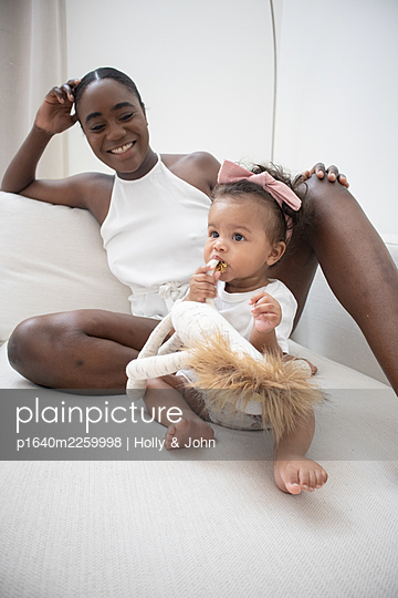 Mother and daughter with cuddly toy - p1640m2259998 by Holly & John