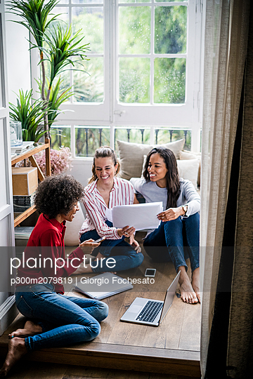 Three women with laptop, cell phone and documents sitting on the floor at home - p300m2079819 by Giorgio Fochesato