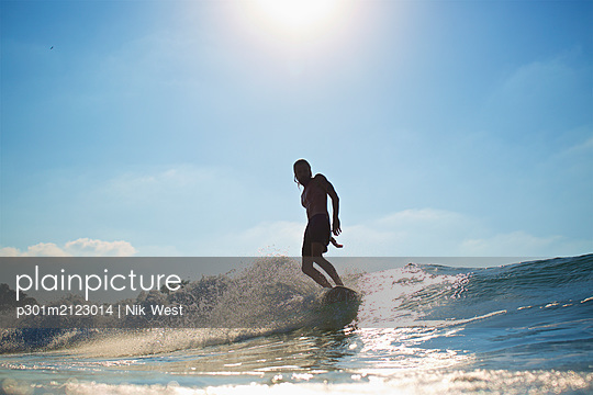 Male surfer riding sunny ocean wave - p301m2123014 by Nik West
