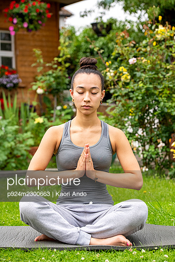 UK, London, Woman meditating on lawn in front of house - p924m2300663 by Kaori Ando
