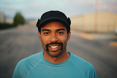 Close-up portrait of smiling man wearing cap while standing on road against sky - p1166m2011566 by Cavan Images