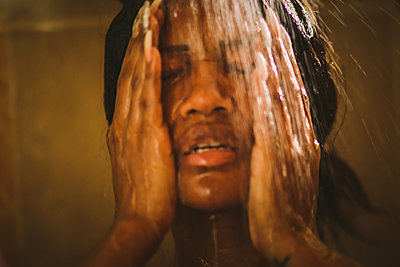 Black woman on shower - p1166m2129844 by Cavan Images