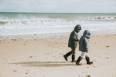 Two boys walking along beach with crashing waves - p1166m2130486 by Cavan Images