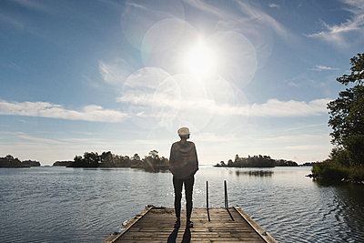 Young woman on landing stage with lens flare - p1477m1586662 by rainandsalt