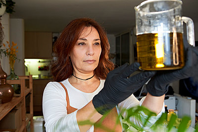 Woman measuring olive oil in beaker while making soap in workshop - p300m2267599 by Veam