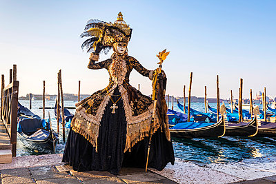 A woman in a magnificent costume poses in front of Gondolas during the Venice Carnival, Venice Lagoon, St. Mark's Square,  Venice, Italy - p651m2033961 by Tim Mannakee