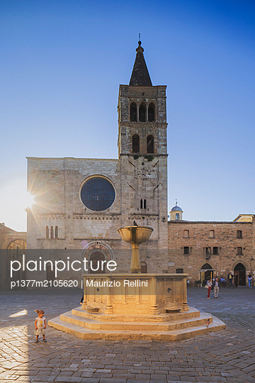 Italy, Umbria, Perugia district, Bevagna, People in Piazza Silvestri at sunset with the medieval fountain and the Cathedral in the background - p1377m2105620 by Maurizio Rellini