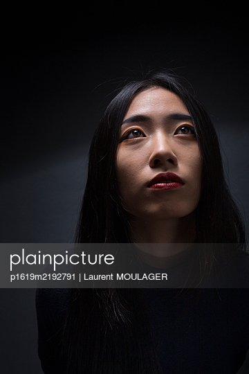 Asian young woamn looking up - p1619m2192791 by Laurent MOULAGER