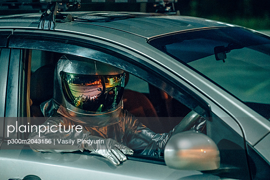 plainpicture - plainpicture p300m2043156 - Spaceman sitting in car at ... - plainpicture/Westend61/Vasily Pindyurin