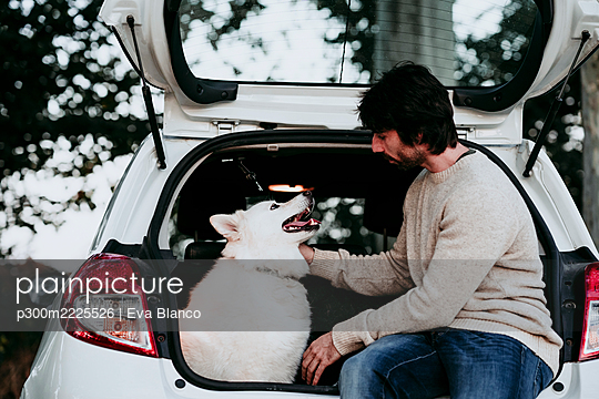 Man sitting with dog in car trunk at forest - p300m2225526 by Eva Blanco