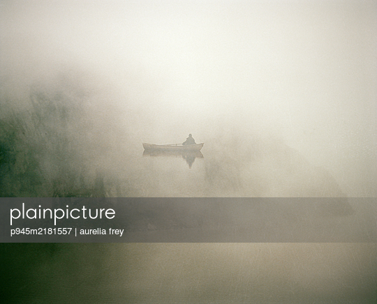 Fisherman with boat in misty landscape - p945m2181557 by aurelia frey