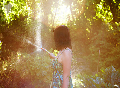Woman watering garden in afternoon sun - p1072m829422 by Neville Mountford-Hoare