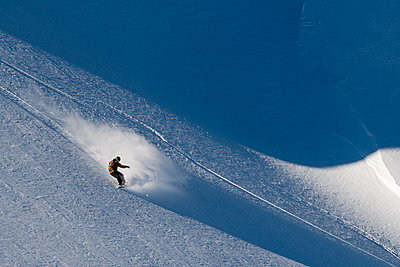 A women snowboards powder on a sunny bluebird day in Argentina. - p1166m2095255 by Cavan Images