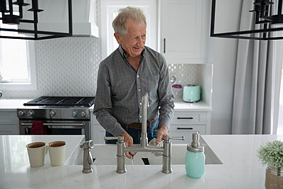 Senior man doing dishes in kitchen - p1192m2109828 by Hero Images