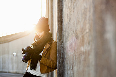 Woman leaning on wall and looking at camera - p1264m1122158f by Astrakan