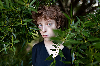 Young woman behind leaves on tree branches - p1427m2169248 by Vyacheslav Chistyakov