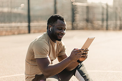 Smiling handsome man using digital tablet while sitting on sports court during sunny day - p300m2277071 by Gustafsson
