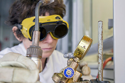 Female chemist with safety glasses and air tank in laboratory - p300m950685f by Sigrid Gombert