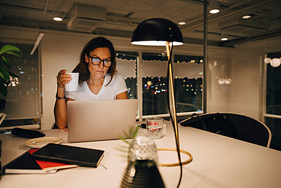 Mature businesswoman holding coffee cup while working late at illuminated creative workplace - p426m2194844 by Maskot