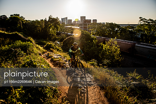 Mountain biker at sunrise with Richmond skyline in the background. - p1166m2269644 by Cavan Images