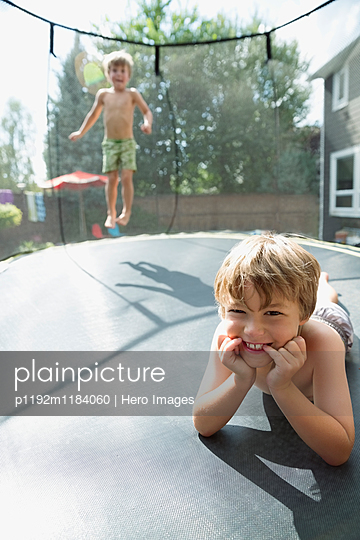 Portrait smiling boys laying and jumping on trampoline in sunny backyard - p1192m1184060 by Hero Images