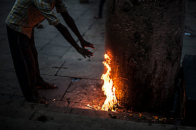 Man warming his hand on a fire - p1007m1144312 by Tilby Vattard