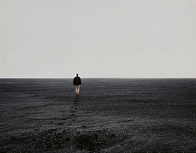Man walking on a black sand beach, South Iceland - p1028m2176259 by Jean Marmeisse