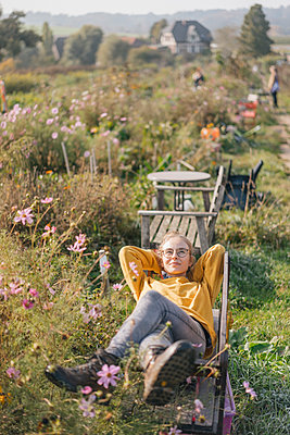 Young woman relaxing in cottage garden - p300m1205786 by Kniel Synnatzschke