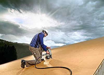 Austria, construction worker fixing medium-density fibreboard - p300m1567834 by Christian Vorhofer