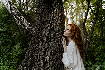 Young redhaired woman hugging tree trunk in the forest - p300m2179936 by VITTA GALLERY