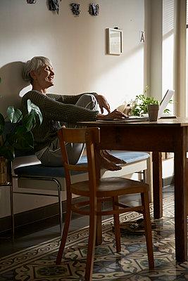Happy senior woman sitting on bench in her kitchen using laptop - p300m2180107 by Stefanie Aumiller