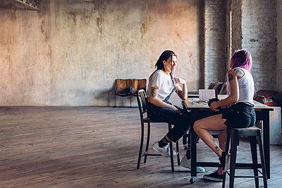 Two creative businesswomen talking in loft office - p300m2202815 by Eugenio Marongiu