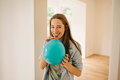 Young woman in new apartment with balloon - p586m1064879 by Kniel Synnatzschke