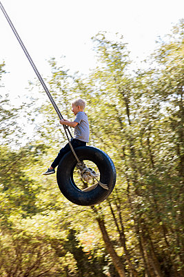 Boy has fun in a tire swing - p756m2125049 by Bénédicte Lassalle