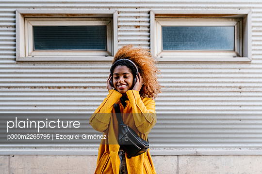 Smiling Afro woman with eyes closed listening music through wireless headphones while standing against wall - p300m2265795 by Ezequiel Giménez