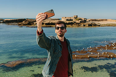Man taking selfie while standing at beach against clear sky - p1166m1554330 by Cavan Images
