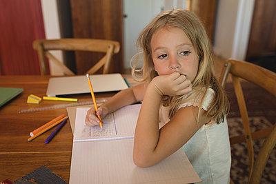 Girl doing her homework at home - p1315m1579139 by Wavebreak