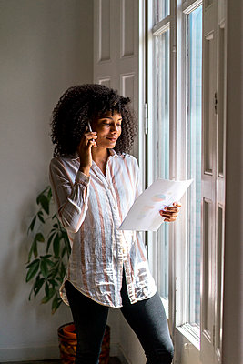 Female Afro entrepreneur with strategy talking on smart phone while standing near window at office - p300m2264510 by VITTA GALLERY