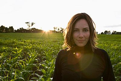 Woman standing amongst new corn crop - p4298192 by Hugh Whitaker