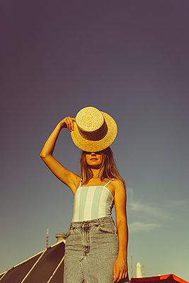 Junge Frau mit Hut auf Hausdach - p432m2260430 von mia takahara