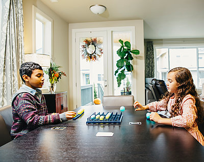 Mixed race siblings playing board game - p555m1305914 by Inti St Clair photography